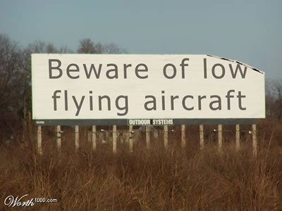 Beware of low flying aircraft sign with corner missing